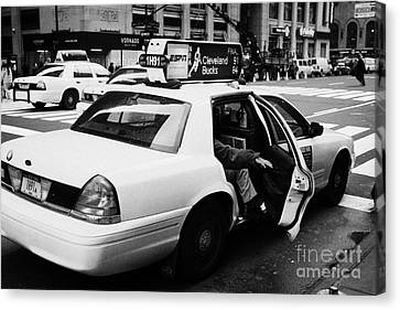 white caucasian passenger closes rear door of yellow cab on taxi rank at crosswalk on 7th Avenue Canvas Print by Joe Fox