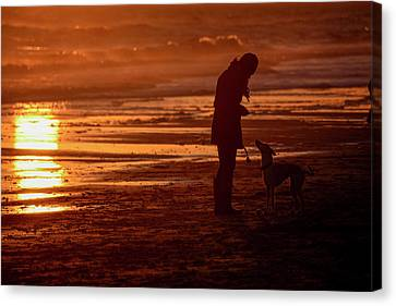 Woman And Dog  On The Beach  At Sunset Canvas Print