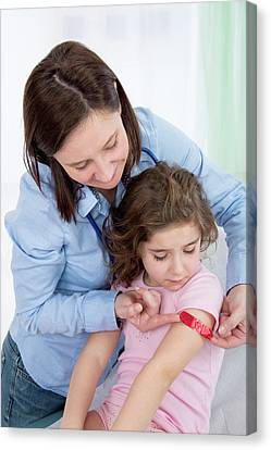 Woman Applying Plaster To Girl's Arm Canvas Print