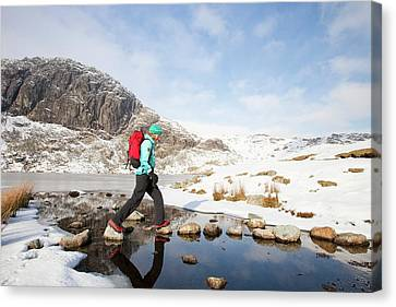 Woman Walker And Frozen Stickle Tarn Canvas Print by Ashley Cooper
