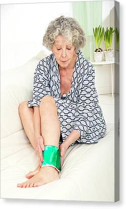 Woman With A Cold Compress On Ankle Canvas Print