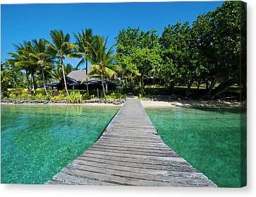 Wooden Pier Leading To A Resort On Aore Canvas Print by Michael Runkel