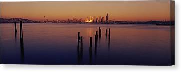 Wooden Posts In The Sea At Dusk Canvas Print by Panoramic Images