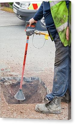 Worker Using A Compressed Air Soil Picker Canvas Print by Ashley Cooper