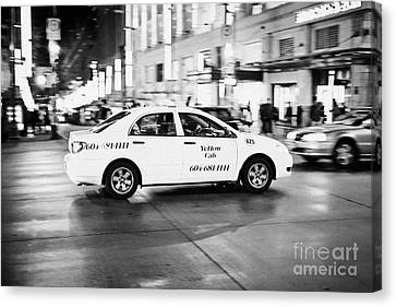 yellow cab taxi crossing junction downtown Vancouver city at night BC Canada deliberate motion blur Canvas Print by Joe Fox
