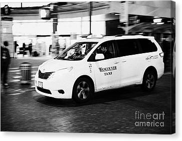 yellow cab taxi downtown Vancouver city shopping area at night BC Canada deliberate motion blur Canvas Print by Joe Fox