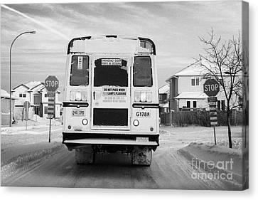 yellow school bus travelling through snow at stop sign Saskatoon Saskatchewan Canada Canvas Print