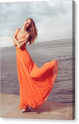 Young Woman In Orange Dress Flying In The Wind At Sea Shore Canvas Print by Oleksiy Maksymenko