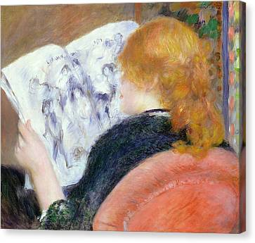 Young Woman Reading An Illustrated Journal Canvas Print by Pierre Auguste Renoir