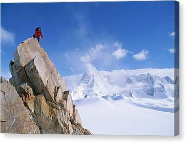 A Mountain Climber Summits Mount Canvas Print by Gordon Wiltsie
