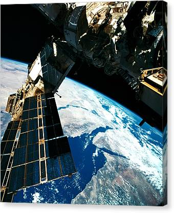 A Satellite Orbiting Above The Earth Canvas Print by Stockbyte