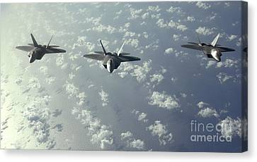 A Three-ship Formation Of F-22 Raptors Canvas Print by Stocktrek Images