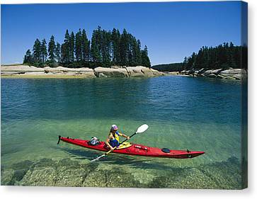 A Woman Kayaks Through The Clear Water Canvas Print