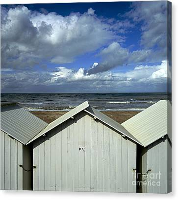Beach Huts Under A Stormy Sky In Normandy Canvas Print by Bernard Jaubert