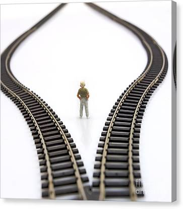 Considering Canvas Print - Figurine Between Two Tracks Leading Into Different Directions  Symbolic Image For Making Decisions. by Bernard Jaubert