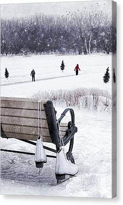 Ice Skates Hanging On Bench With People  Skating In Background Canvas Print by Sandra Cunningham