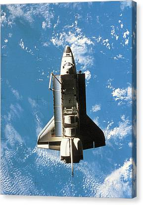 Space Shuttle Orbiting Above Earth Canvas Print by Stockbyte