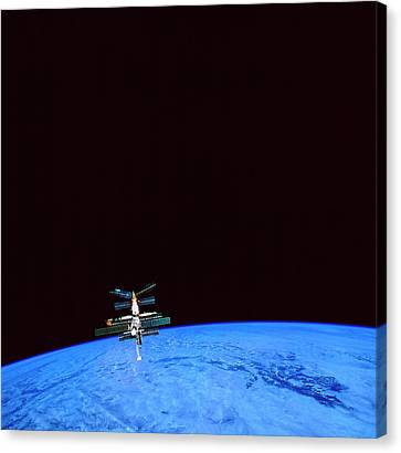 Courage Canvas Print - A Space Station Orbiting Above The Earth by Stockbyte