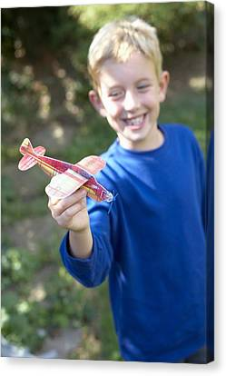 Boy Playing With A Toy Aeroplane Canvas Print by Ian Boddy
