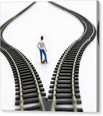 Figurine Between Two Tracks Leading Into Different Directions Symbolic Image For Making Decisions. Canvas Print by Bernard Jaubert