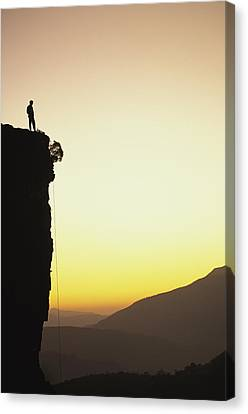 A Climber Stands Atop A Cliff Canvas Print by Bill Hatcher