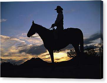 Santa Fe Cowgirl Canvas Print - A Cowboy Silhouetted Against A Sunset by Stephen St. John