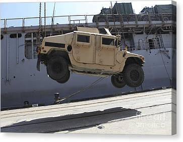 A Crane Lifts An M998 Humvee Canvas Print by Stocktrek Images