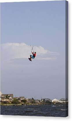A Kiteboarder Jumps High Over Beach Canvas Print by Skip Brown