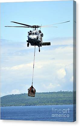 A Mh-60 Knighthawk Carries Supplies Canvas Print by Stocktrek Images