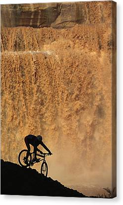 A Mountain Biker Pedals Past Rushing Canvas Print by Bill Hatcher
