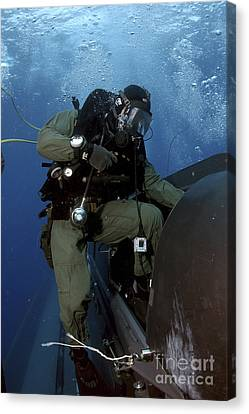A Navy Seal Climbs Aboard A Seal Canvas Print by Stocktrek Images
