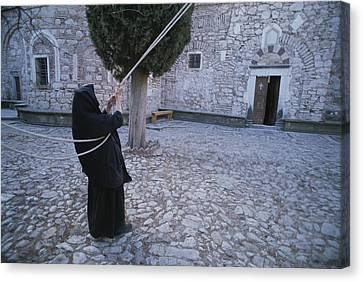 A Nun Pulls On Ropes In A Courtyard Canvas Print by Tino Soriano