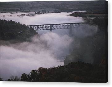 A Railroad Bridge Crosses A Fog-bound Canvas Print