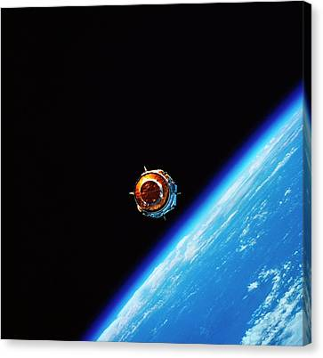 A Satellite In Orbit Above Earth Canvas Print by Stockbyte