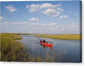 A Sea Kayaker And Fisherman Paddles Canvas Print by Skip Brown