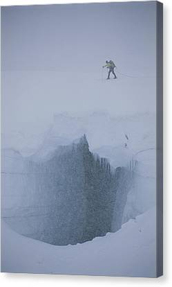 A Skier Above A Deep Glacier Crevasse Canvas Print by John Burcham