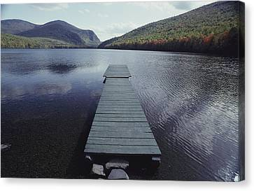 A Small Dock Leads Out To Placid Waters Canvas Print by Bill Curtsinger