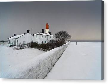 A Snow Covered Fence With A Lighthouse Canvas Print by John Short