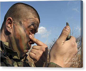 A Soldier Applying Face Paint Prior Canvas Print by Stocktrek Images
