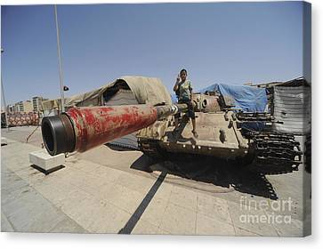 A T-55 Tank With Two Children Playing Canvas Print by Andrew Chittock