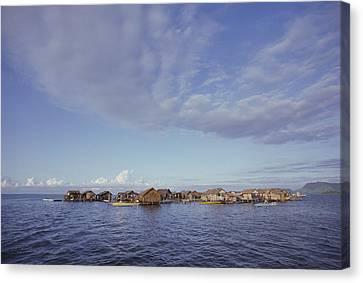 A Tiny Village Of Huts Over The Water Canvas Print by Tim Laman