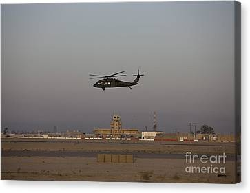 A Uh-60 Blackhawk Helicopter Flies Canvas Print by Terry Moore