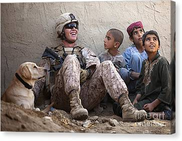 A U.s. Marine Jokes With Afghan Canvas Print by Stocktrek Images
