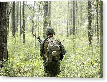 A U.s. Marine Patrols Through A Forest Canvas Print by Stocktrek Images