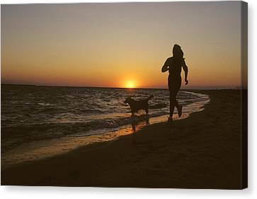 A Woman And Her Dog Running Canvas Print by Skip Brown
