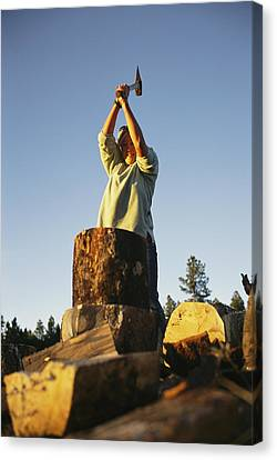 A Woman Chops Wood With Canvas Print by Bobby Model