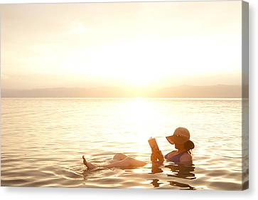 A Woman Reads A Book While Floating Canvas Print by Taylor S. Kennedy