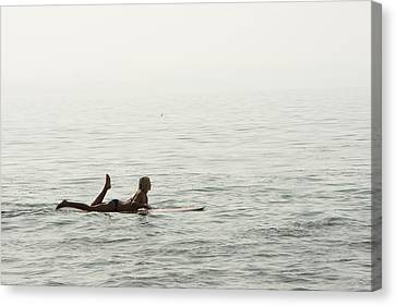 A Woman Rests On Her Surfboard Waiting Canvas Print by Tim Davis