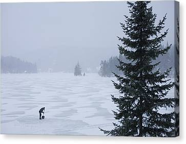 A Woman Shovels A Rink On A Lake Canvas Print by Taylor S. Kennedy