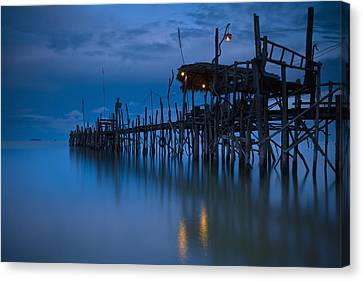 A Wooden Pier With Lights On It At Canvas Print by David DuChemin